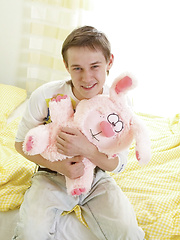 Adorable twink plays around with a cute toy and his big rod in the bedroom