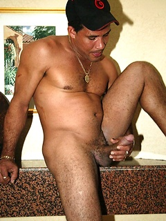 Handsome Latino guy removes his clothes and tugs hard on his fat meat pole