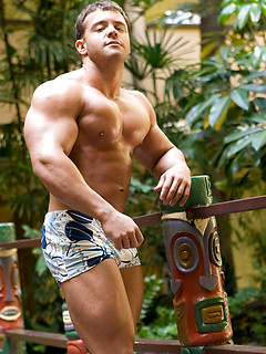 Body builder flexes by the waterfall in his swimsuit and his muscles look amazing