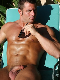 His body is coated with tanning oil as the muscular hunk jerks off outdoors