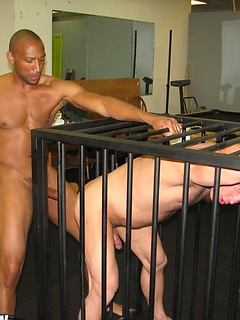 White bottom boy in a cage sucks and gets fucked bareback by a big black cock