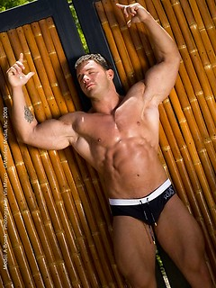 Bodybuilder glistens outdoors as he flexes his perfect muscles for us