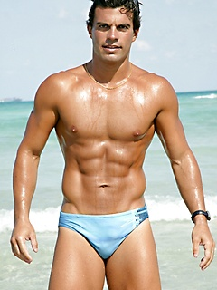 Hunk on the beach in a sexy swimsuit has a world class tanned body
