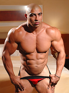 Hunk of a man Oscar Navarro flexes his muscles while wearing revealing speedos