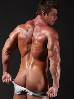 Cock and balls bulge against his skintight shorts as the body builder flexes