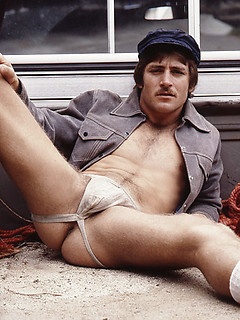 Vintage gay photo shoot with a man in a jockstrap and mustache