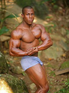 Gorgeous black body builder with perfectly cut muscles flexes in paradise