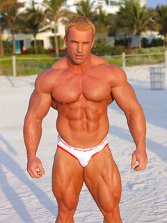 Blonde Australian stud flexes his big muscles at the beach while wearing speedos