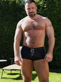 Solo bear Marc Angelo hangs out poolside and plays with his cock