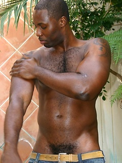 Ripped black stud applies oil to his hot body before unveiling his huge member