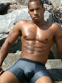 Muscular ebony stallion strips down to his sexy underwear at the beach