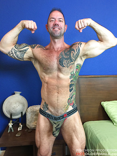 Tattooed gay dude likes to jerk his massive cock while he poses on the bed