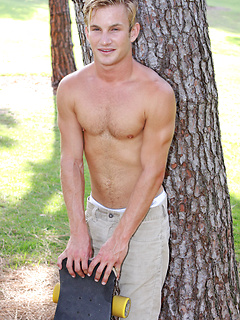 Young gay model with great hair and a charming smile skates and strips outdoors