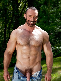 Strong dude Brad Kalvo slowly starts stripping to unveil his cock outdoors