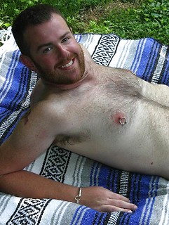 Pierced nipples and cock look sexy on the hairy bearded guy posing on a picnic blanket
