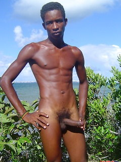 Skinny black gay model on the beach for a striptease and shots of his growing cock