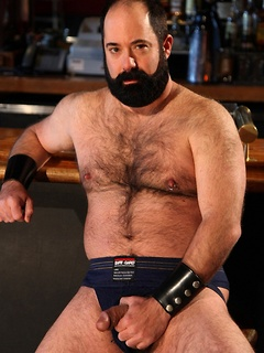 Bearded bear in leather and blue jeans strips from his stool at the bar