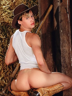 Cute farm boy strips off his tank top and jeans as he plays among the bales of hay