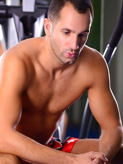 Hot model Rogerio Matteo sits in the gym and shows off his rock hard cock
