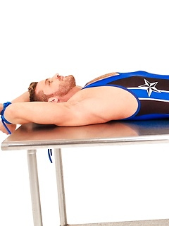 Hot wrestler tied to a table in his spandex outfit struggles against the bondage