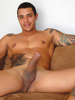 Tattooed hottie Coyote smiles and plays with his gorgeous growing cock