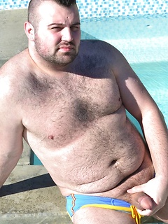 Solo bear Rex Blue sits by the pool in his skimpy swimsuit and jerks off