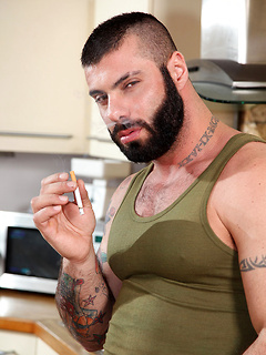 Hot bear with a beard smokes a cigarette and strips to show off that world class body