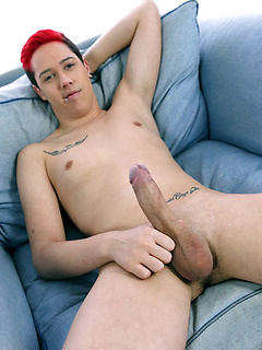 Pierced and tattooed young guy with dyed hair is happy to show off his asshole