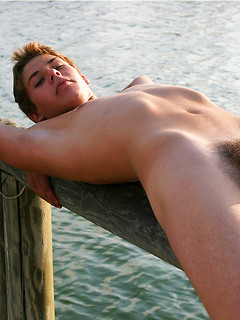 Young gay boy takes off the clothes outdoors to expose his stiff shaft