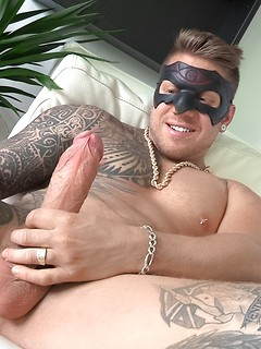 Half his torso is covered by an artful tattoo as the masked dude gets a handjob