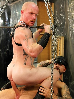 Gay leather hunk fucks his submissive bottom without a condom